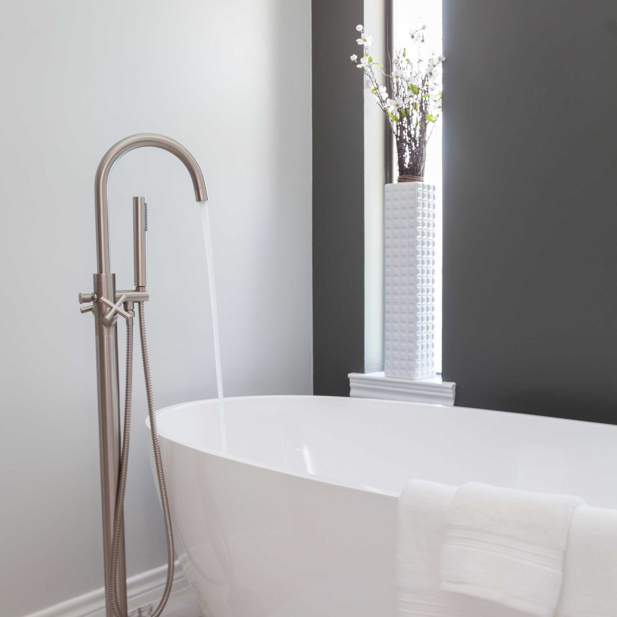 Free standing bathtub, tub filler, modern bathtub and bathroom, black and white accent tile, window over tub